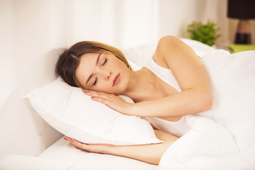 Young Woman in White Shirt Sleeps in Bed at Home.