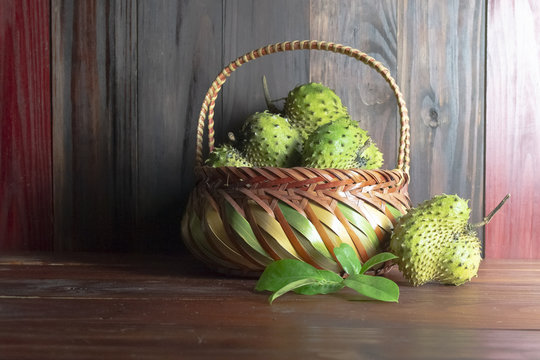 Soursop in basket or Prickly Custard Apple or Annona muricata L on wooden table and wooden wall