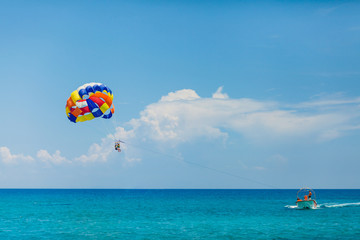 People flying on a colorful parachute towed by a motor boat