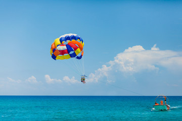 Poster Water Motor sporten People flying on a colorful parachute towed by a motor boat