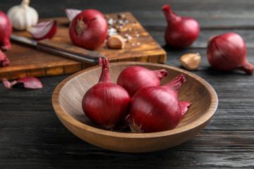 Plate with ripe red onions on wooden table