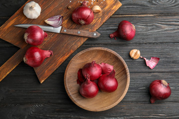 Flat lay composition with ripe red onions on wooden table