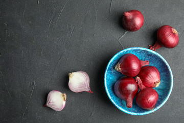 Bowl with ripe red onions on table, top view