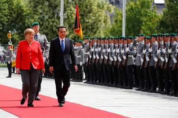German Chancellor Angela Merkel and Chinese Prime Minister Li Keqiang review the guard of honour at the chancellery in Berlin