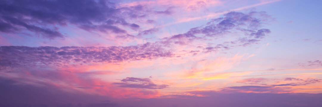 Panoramic view of a pink and purple sky at sunset. Sky panorama background.