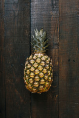 Ripe pineapple on dark wooden background. Tropical fruit creative concept.