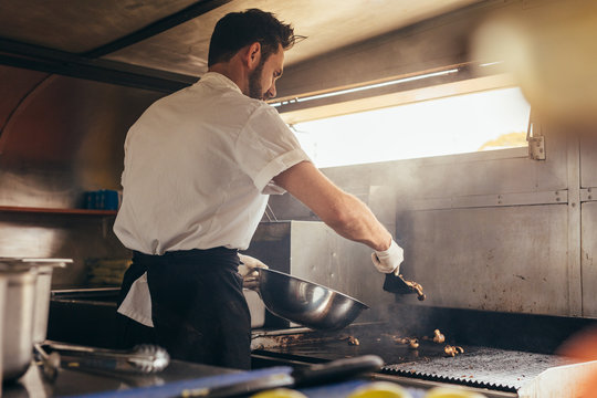 Male cook preparing a dish in food truck
