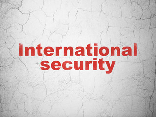 Protection concept: Red International Security on textured concrete wall background