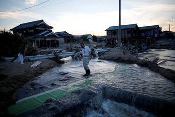A local resident walks in a flooded area in Mabi town in Kurashiki