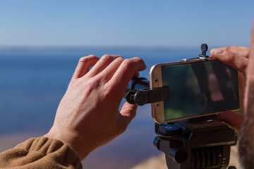 A man adjusts the smartphone on a tripod with lenses. The photographer travels taking pictures of the landscape using a mobile phone