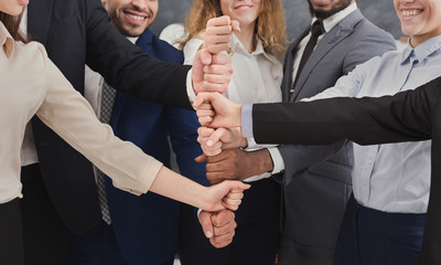 Positive business people putting fists on top of each other