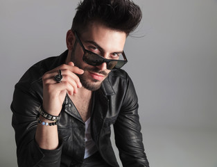 portrait of seductive man wearing leather jacket looking over sunglasses