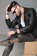 side view of man in leather jacket sitting and thinking