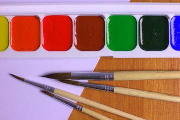 Watercolor Set with Different Brushes and blank paper on the Table