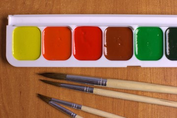 Watercolor set with different brushes on the table