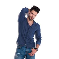 sensual man wearing a navy shirt posing while standing