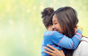 family, motherhood and people concept - happy mother and daughter hugging over green holidays lights background