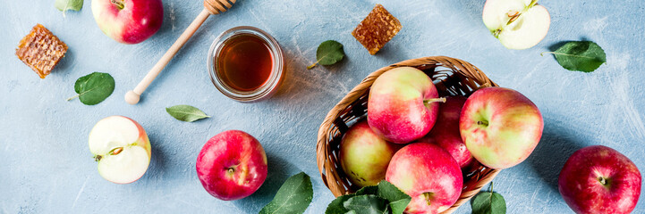 Jewish holiday Rosh Hashanah or apple feast day concept, with red apples, apple leaves and honey in jar, light blue background copy space above banner