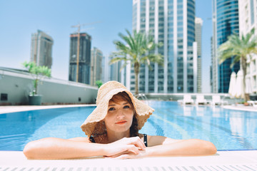Young woman wearing straw hat relaxing in swimming pool