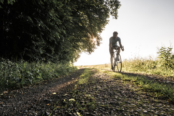 Rennradfaher im Sommer bei Sonnenuntergang