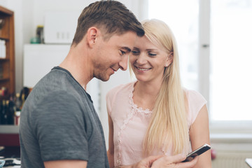 Young couple smiling happily at their mobile