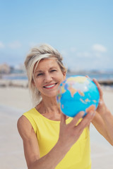Happy blond woman holding up a world globe