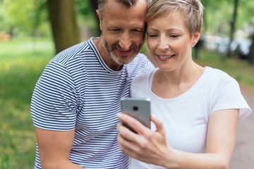Mature couple reading an sms on their mobile
