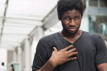 man suffering from acid reflux or GERD; sick stressed guy with indigestion, acid reflux or gerd symptoms; man health care, body care, sickness, pain concept; adult african man or black man model