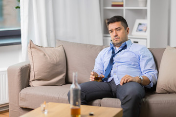 alcoholism, alcohol addiction and people concept - male alcoholic with glass drinking whiskey at home