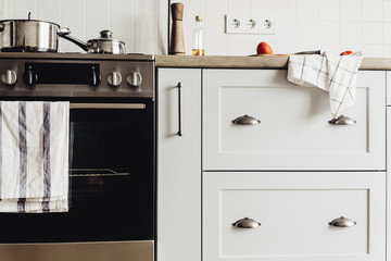 Kitchen design in modern scandinavian style. stylish light grey kitchen interior with modern furniture and contemporary handles and stainless steel appliances in a new house