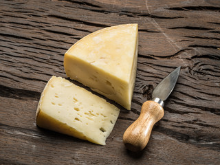 Pieces of homemade cheese on the wooden background.