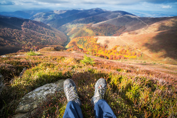 Hiker's boots and the mountain peaks at the background.