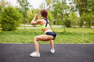 Sport girl in sportswear doing squatting in the park.