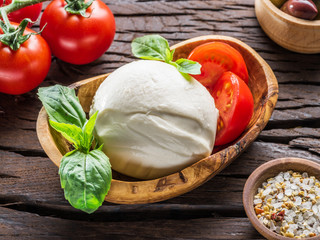 Buffalo mozzarella in the wooden bowl and cherry tomatoes on the table.