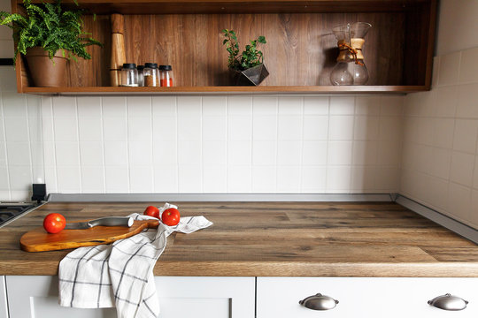 wooden board with knife, tomatoes on modern kitchen countertop and shelves with ingredients spices in glass jars. cooking food. Stylish gray kitchen interior design in scandinavian style