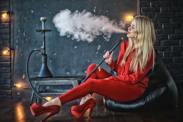girl smokes  hookah / beautiful glamorous girl in red dress smokes a hookah, the sexy model in a night club smokes