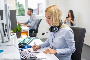 Beautiful businesswoman with headset analyzing business document at office desk