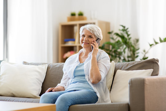 technology, communication and people concept - happy senior woman calling on smartphone at home