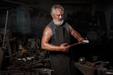The portrait of blacksmith preparing to work metal on the anvil