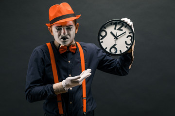 scary clown pantomime with a clock in his hands, on a dark background