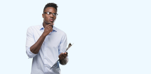 Young african american man holding a clipboarad serious face thinking about question, very confused idea