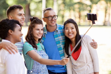 people, friendship and international concept - happy smiling young woman and group of happy friends taking picture by selfie stick in park