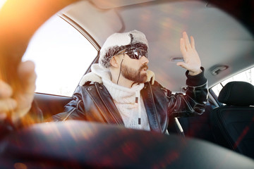 driver of the car in winter clothes, man behind the wheel, a winter journey on car,  brutal man with  beard on the car,  professional traveler