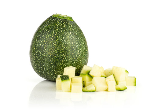 One whole round zucchini and chopped pieces isolated on white background fresh summer squash.