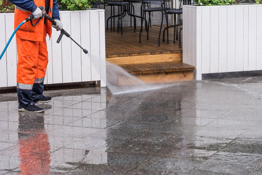 Worker cleans the sidewalk in front of a street cafe
