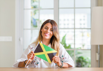 Young woman at home holding flag of Jamaica with a happy face standing and smiling with a confident smile showing teeth