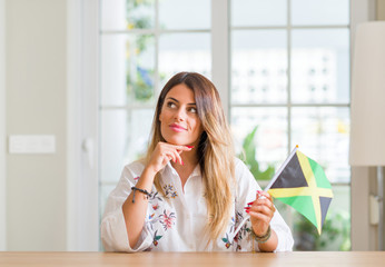 Young woman at home holding flag of Jamaica serious face thinking about question, very confused idea
