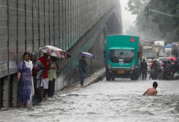 People wade through a waterlogged street during heavy rains in Mumbai