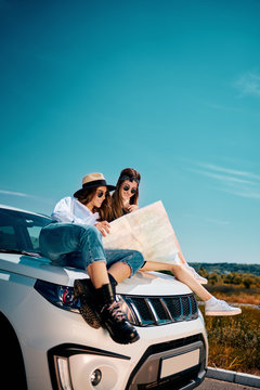 Two young females sitting on car hood looking at map