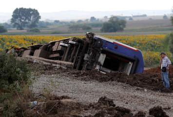 A man talks on his mobile phone at the scene where a passenger train derailed on Sunday, near Corlu in Tekirdag province